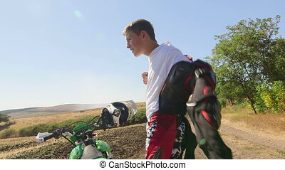Young enduro racer dressing motorcycle protective gear...