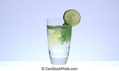 adding a sprig of mint in a mojito - closeup with white...