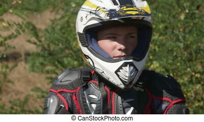 Face of young enduro racer in motorcycle protective gear...