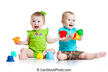 Adorable babies playing with color toys. Children girl and boy sitting on floor. Isolated on white background.
