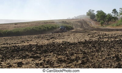 New tractor using disk harrows to till a field long shot