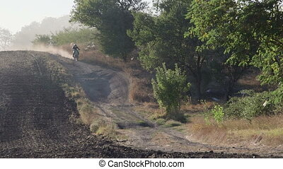 Enduro racer riding motorcycle on dirt track kicking up dust...
