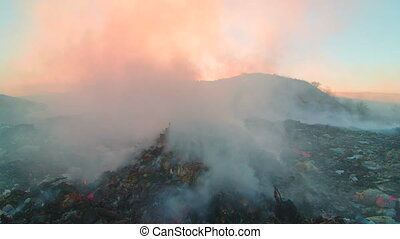 Burning pile of garbage at dump site toxic smoke rises into the air