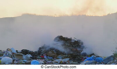 Toxic smoke from burning dump rises into the air pan shot