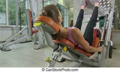 Fit young woman training in health fitness club on leg press...