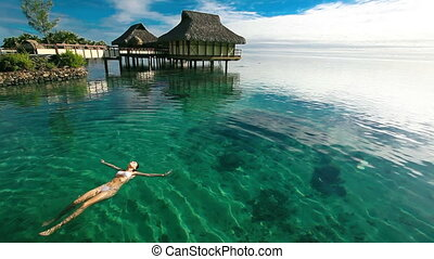 woman swimming in tropical lagoon - woman swimming in...