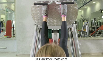 Young woman training in health fitness club on leg press...