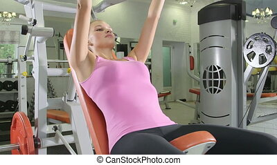 Young woman training in free weights area at health fitness...