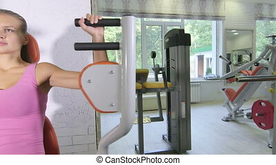 Weight training workout on exercise machine in health fitness club