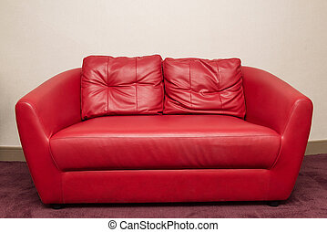 Red sofa in the room, white wall