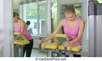 Young woman training on standing leg curl machine in health fitness club