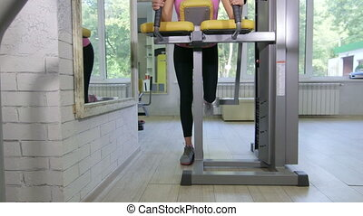 Fit young woman training in health fitness club on standing...