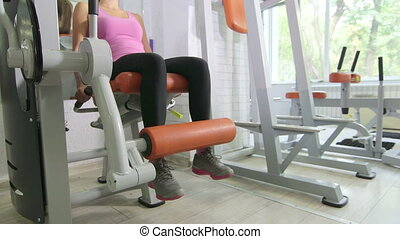 Seated leg extension machine exercise in health fitness club