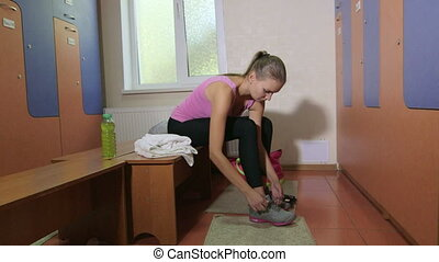 Young woman tying up sneakers in fitness club locker room
