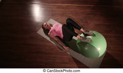 Fit girl exercising at fitness club with stability ball for...