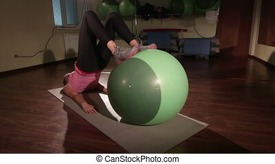 Fit girl exercising at fitness club with stability ball for core training