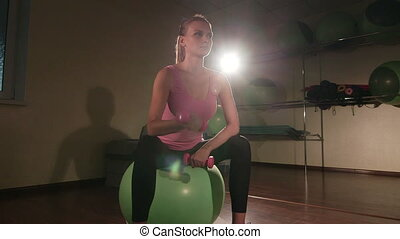 Young fit woman with light dumbbells exercising on fitness ball