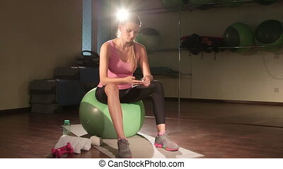 Young woman injured knee during fitness workout in gym applying pain relief gel