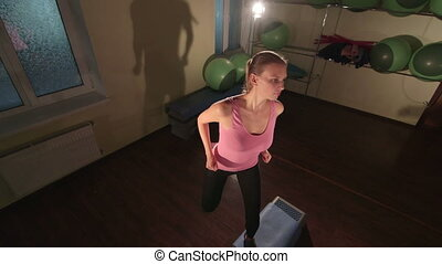 High-angle shot of fit woman doing step aerobics exercise in fitness club