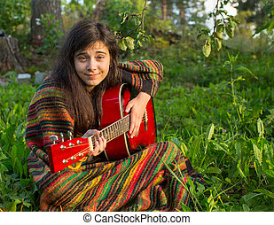 Young girl plays guitar sitting on the grass in the Park