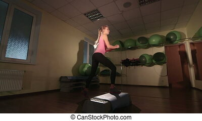 Low-angle shot of young woman training in gym doing step aerobics