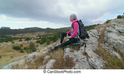 JIB CRANE: Woman hiker with backpack relaxing on top of...