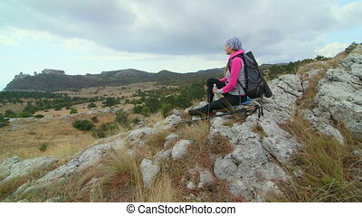 Woman hiker with trekking poles looking at majestic mountain...