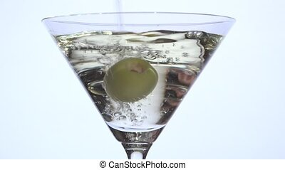 Pouring martini dry over olive - closeup with white...