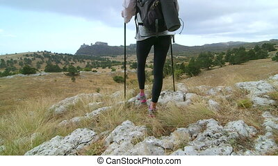 Day hiking woman standing on edge of cliff at plateau mountain peak