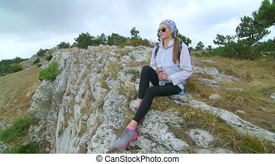 Day hiking young woman on cliff enjoying view at bare stone...