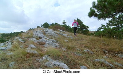 JIB CRANE: Fit young woman trail running in the mountains