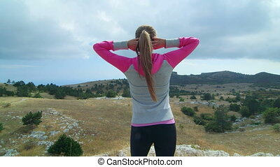 JIB CRANE: Fit young woman in sportswear on top of mountain...