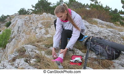 Young hiking woman sprained ankle using first aid kit applying bandage