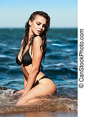On a beach - Sexy brunette girl in black bikini posing on a...