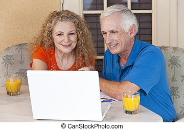 Senior Man and Woman Couple Outside Using Laptop Computer -...