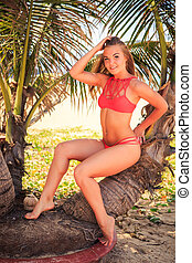 blond girl in bikini sits on palm smooths hair smiles -...