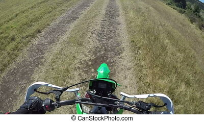 Point of View: Enduro biker riding motorcycle on dirt track...