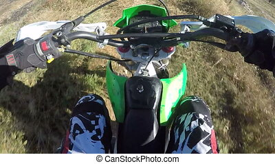 Point of View: Enduro rider riding motorcycle on dirt track