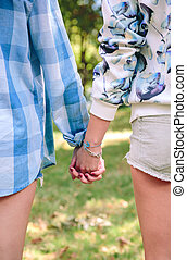 Closeup of women holding hands over nature background.