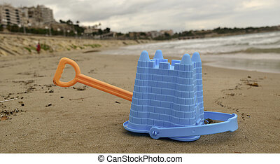 abandoned toy shovel and bucket on the beach
