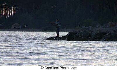fisherman is throwing the bait into sea water, standing on...