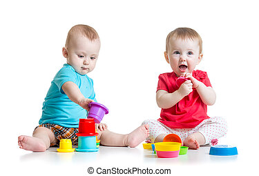 Cute babies playing with color toys. Children girl and boy sitting on floor. Isolated on white background.