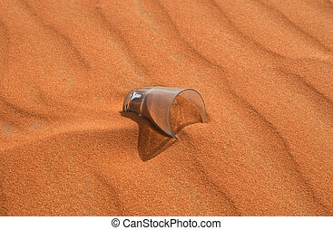 Empty glass in the sand