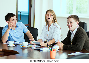 Young business woman with business partners, men at a...