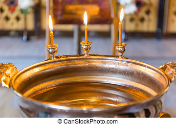 font for baptism - burning candles on the baptismal font for...