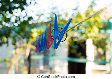 Clothespins on a wire in the yard. Nearest clothespin in...