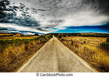 country road under a dramatic sky in hdr