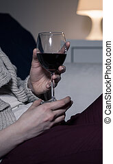 Woman holding glass of red wine, vertical