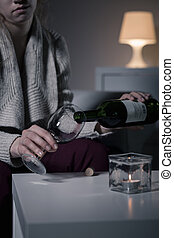 Woman pouring wine into glass - Young sad woman pouring wine...