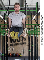 Gymnastic rings workout - Young man practicing gymnastic...